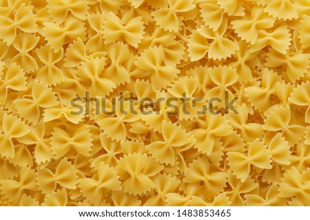 Dry uncooked farfalle pasta as a background. Flat lay.