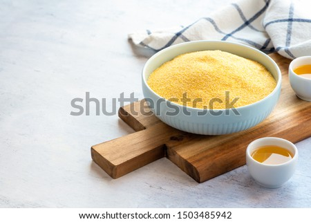 Dry uncooked polenta in a bowl on a cutting board and olive oil, gray background. Traditional italian food, vegetarian food.