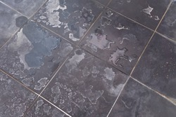 Dry water stains on the tile floor in the bathroom