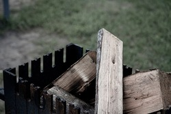 Dry wood logs in rustic fireplace. Black metal grill with firewood inside. Grilling and camping in a park. Summertime picnic. Selective focus on the texture of the wood, blurred background.