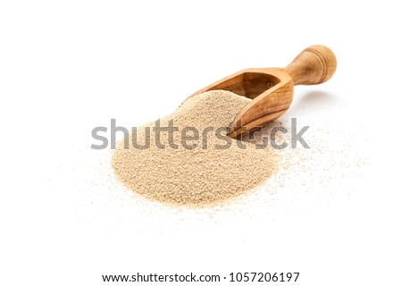 Dry yeast in wooden scoop on white background