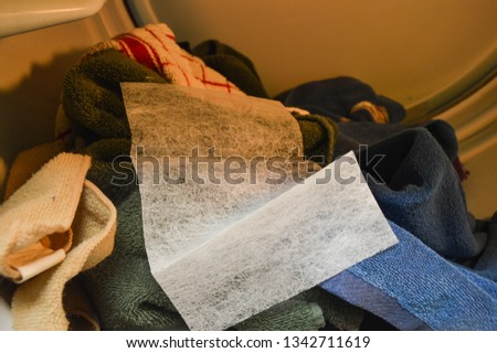 Dryer sheet in dryer used as a fabric softener, dryer sheet in dryer on towels and clothing, white dryersheet