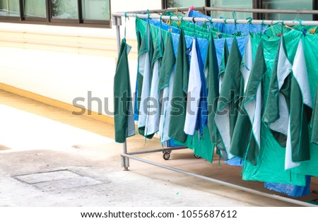 Drying green plastic dresses on the hangers in sunlight of sunny day, the dresses for using in surgical room of the rural hospital, Thailand. The simple way of energy saving.
