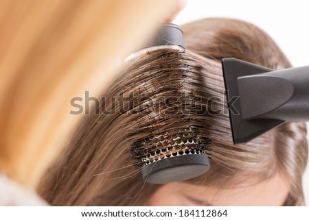 Drying long brown hair with hair dryer and round brush.