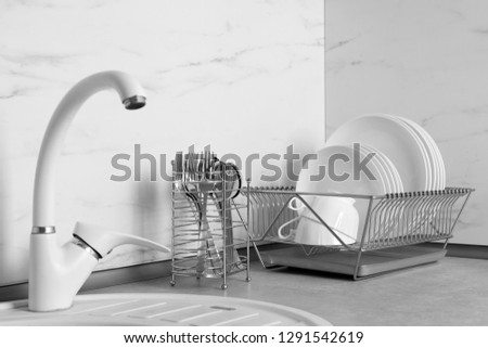 Drying rack with clean dishes and cutlery holder near sink in kitchen