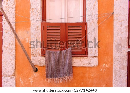 Drying towel on rope against orange weathered wall. Closed window with shutters on old wall with drying linen. Building facade in Portugal. Travel concept. European architecture. Portuguese lifestyle. #1277142448