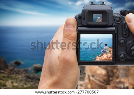 DSLR camera in hand shooting solitary man on top of the coast watching the sea - photos made by me, you separately can find on my shutterstock portfolio. Logos has been deleted to be 100% commercial.  #277700507