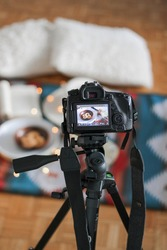 DSLR camera on tripod during food photography sesion at home including aztec blanket, cookies, and led lights.