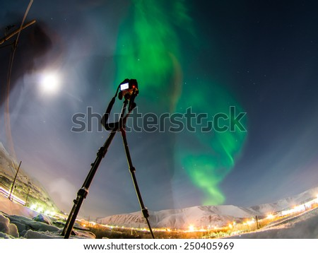 DSLR Camera on tripod shooting amazing green aurora borealis (northern lights) in moonlit night