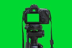 Dslr camera with green screen on the tripod isolated on green background. Green screen camera