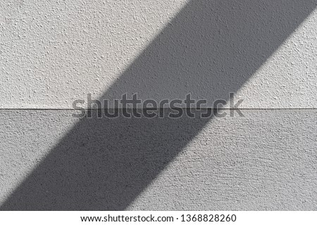 Dual toned of vintage of grey and dark grey stone wall, Outdoor building with light and shadow in the middle in diagonal lines, Cement concrete texture background.