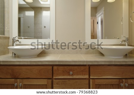 Dual vessel porcelain sinks are set on a wooden vanity with a tiled counter. There are mirrors set above each sink. Horizontal shot.