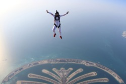 Dubai adventure sky fly.Adrenalin adventure flying in Skydive Dubai. Men in white suit fly above palm. Adventure background in the air