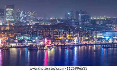 Dubai creek landscape night timelapse with boats and yachts and modern buildings with traffic on the road. Aerial top view from above