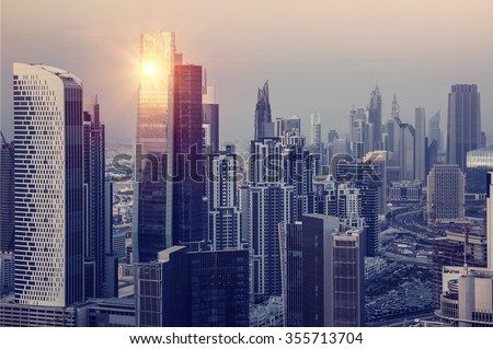 Dubai downtown in the evening, luxury modern buildings in bright yellow sunset light, futuristic cityscape of United Arab Emirates