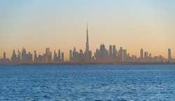 Dubai Downtown skyline with waves on sea beach, United Arab Emirates or UAE. Financial district in travel vacation concept. Urban city. Skyscrapers buildings with sunset sky.