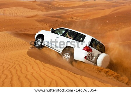 DUBAI - JUNE 2: Driving a 4-wheel drive SUV on the desert, traditional entertainment for tourists on June 2, 2013 in Dubai