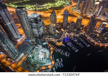 Dubai Marina by night. Amazing Dubai skyline, skyscrapers. Dubai Marina from above. Night city lights. Skyscraper construction. Cayan tower view.