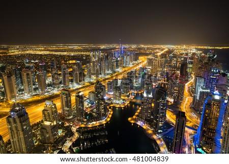 Dubai Marina by night. Dubai aerial view. Dubai skyscrapers. Rooftop view. Dubai luxury homes. Dubai Emaar properties buildings. Jumeirah lakes towers. Dubai skyline. Night cityscape.Sheikh Zayed road