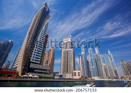 Dubai Marina with boat against skyscrapers in Dubai, United Arab Emirates