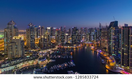 Dubai Marina with yachts in harbor and modern towers from top of skyscraper transition from day to night , Glittering lights and tallest skyscrapers during a clear evening with Blue sky.  #1285833724