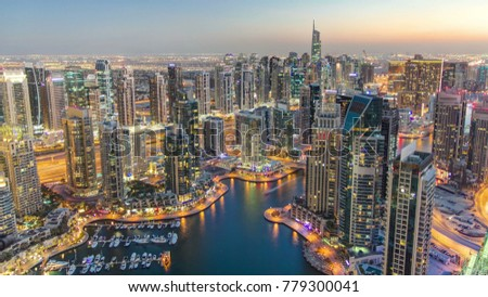 Dubai Marina with yachts in harbor and modern towers from top of skyscraper transition from day to night timelapse, Glittering lights and tallest skyscrapers during a clear evening with Blue sky. 4K #779300041