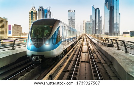 Photo of  Dubai metro train on rails at background of skyscrapers. Famous outdoor subway Red Line.