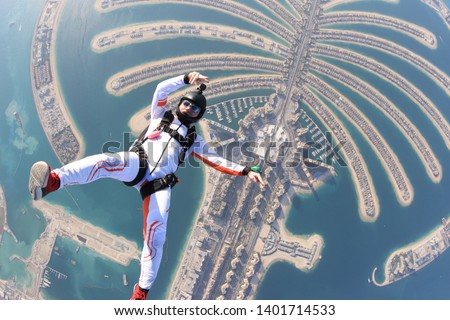 Dubai.People lies on beach Dubai Palm in free fall sky jump. Sea outdoor skydiving travel. Free fall extreme action man on speed 200km/h. Summer beach sky advertising.