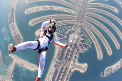 Dubai.People lies on beach Dubai Palm in free fall sky jump. Sea outdoor skydiving travel man. Free fall extreme action sky man on speed 200km/h. Summer fly beach sky man advertising business.