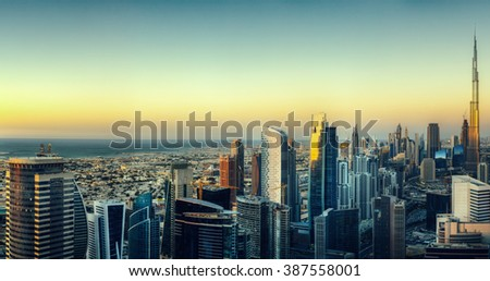 Dubai\'s business bay with many modern skyscrapers. Beautiful aerial cityscape by colorful sunset.