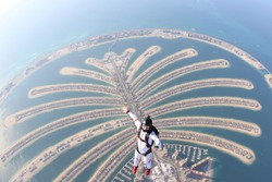 Dubai sea. Skydiving travel men stand on Dubai palm in free fall. Skydive Dubai. Skydiving tourism and free fall in summer