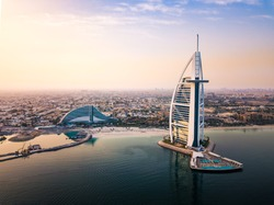 Dubai seaside skyline and Burj Al Arab luxury hotel aerial view at sunrise