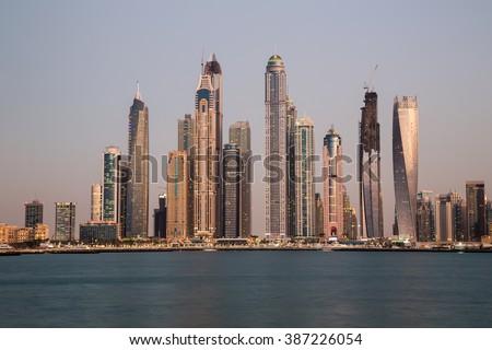 Dubai skyline, cityscape. Dubai Marina skyscrapers Cayan Tower, Princess Tower, Marina 101. Palm Jumeirah views, sunset colors. Dubai skyscrapers. Dubai sunset.