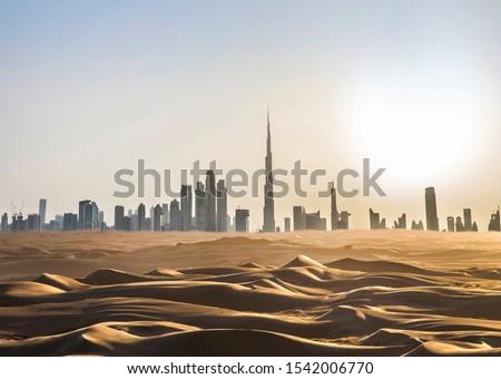 Dubai skyline in the desert at sunset. United Arab Emirates.