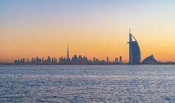 Dubai, UAE - 03/30/2020 : Burj Al Arab in Jumeirah Island or boat building with waves on sea beach, Downtown skyline. Financial district in urban city. Skyscrapers at sunset.