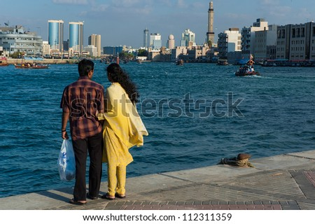 DUBAI, UAE - DECEMBER 31: A young couple  enjoys the view of Dubai Creek on December 31, 2004 in Dubai, UAE. Indians in the UAE constitute a large part of population of the country.