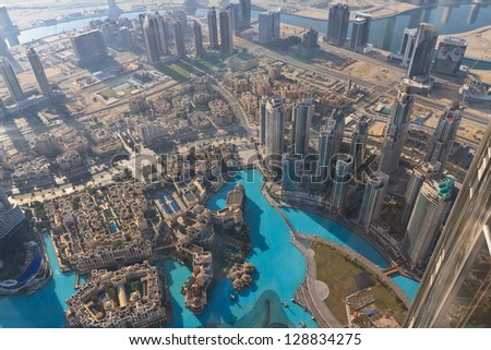 DUBAI, UAE - JANUARY 6: Aerial view of Downtown Dubai with man made lake and skyscrapers on January 6, 2013 in Dubai, UAE. View from the height of Burj Khalifa. - stock photo