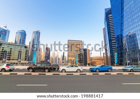 DUBAI, UAE - MARCH 30: Traffic on the streets of Dubai Marina on March 30, 2014, UAE. Dubai Marina is a district in Dubai with artificial canal skyscrapers who accommodates more than 120,000 people.