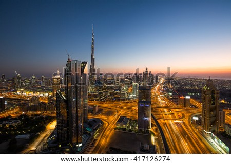 DUBAI,UAE - NOVEMBER 13, 2015: Dubai skyscrapers, sunset sky. Dubai  downtown evening skyline. Burj Khalifa tallest building in the world. Dubai by night. Dubai roads, highways. Interchange 1. #417126274