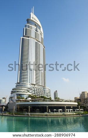 DUBAI, UAE - OCTOBER 22, 2014: The curving architecture of The Address Downtown Dubai residential tower overlooks the green waters of the manmade Burj Lake.