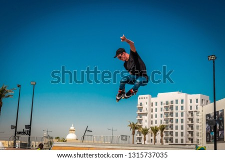 Dubai, United Arab Emirates - 02/07/2019: A man on roller blades does a grab trick while jumping off a ramp at a skate park in Dubai #1315737035