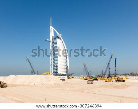 DUBAI, UNITED ARAB EMIRATES - JAN 25, 2014: Cranes and work in progress on construction site near Burj al Arab Hotel, Jumeirah Beach in the city of Dubai, United Arab Emirates