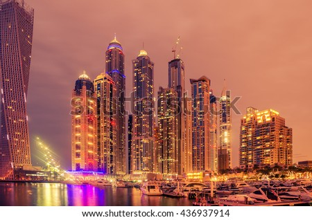 Dubai, United Arab Emirates: skyscrapers of famous Marina at night. This is an artificial canal city, built along a stretch of Persian Gulf shoreline. Fireworks in the background of  picture.