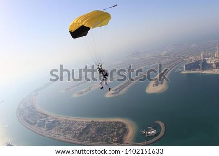 Dubai. Yellow extreme skydiving activity fun people on Dubai palm Jumeirah. Skydive Dubai jump. Yellow parachute jump. Summer sky activity. Big goal