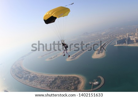 Dubai. Yellow extreme skydiving fun people on Dubai palm Jumeirah. Skydive Dubai jump. Yellow parachute jump. Summer sky. Big goal