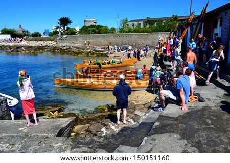 DUBLIN, IRELAND – JUNE 9: Unidentified competitors and onlookers at The East Coast Rowing Council Races on June 9, 2013 in Sandycove, Ireland. Wooden racing skiffs lie along the shoreline.
