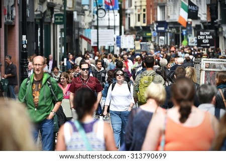 DUBLIN - JUL 22: Crowds of people walk on Grafton Street on Jul 22, 2015 in Dublin, Ireland. The street is a main tourist attraction in the Irish capital, renowned for its lively atmosphere and shops. #313790699