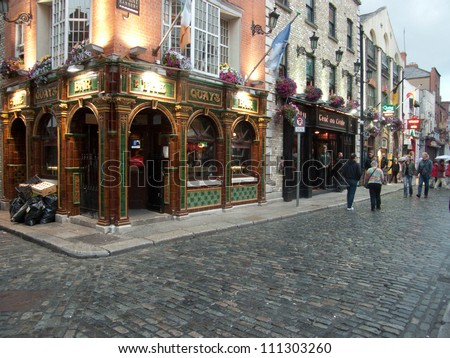 DUBLIN - JUL 27: Unidentified people walk by many bars and pubs in famous Temple Bar quarter on Jul 27, 2009 in Dublin, Ireland. Temple Bar has preserved medieval street pattern, with narrow streets.