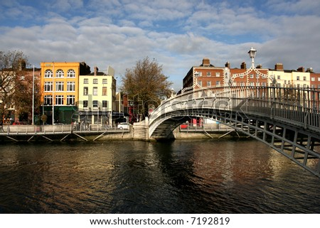 Dublin landmark - Ha'penny bridge on Liffey River. Rows of colorful houses.