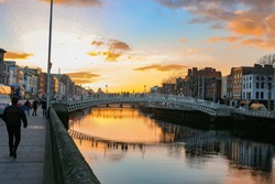 Dublin night scene with Ha'penny bridge and Liffey river lights . Ireland. A very popular spot to visit while you are in Dublin. this bridge formerly charged half a penny to cross hence the name.